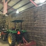 Hay stacked in storage area with tractor